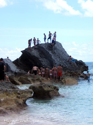 Lots of people climbing on a giant rock in the Bermuda ocean