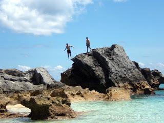 Man jumping off of giant rock in Bermuda ocean