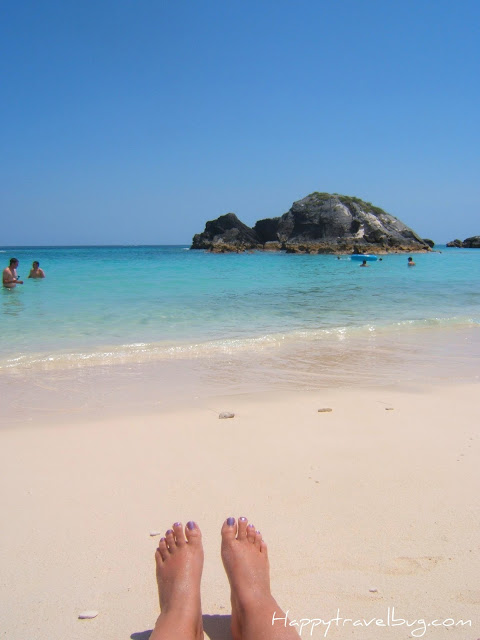 Pink Sand beach in Bermuda with a woman's feet showing on the sand