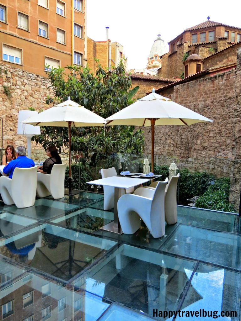 Clear glass floor with modern white chairs and white umbrellas in Barcelona