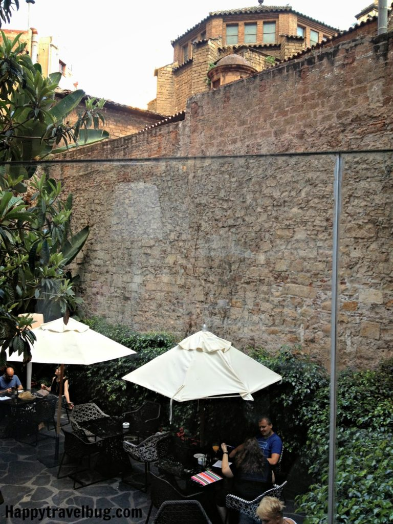 Outdoor seating with umbrellas next to an old city wall in Barcelona