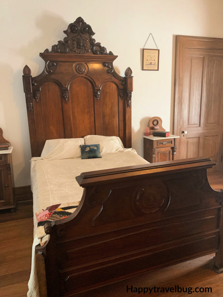 Antique wooden bed with a white bedspread