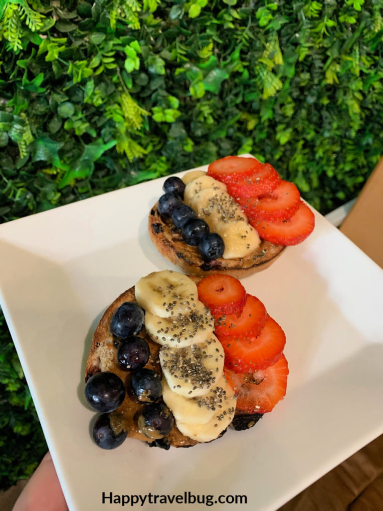 bagel with blueberries, bananas, and strawberries on it