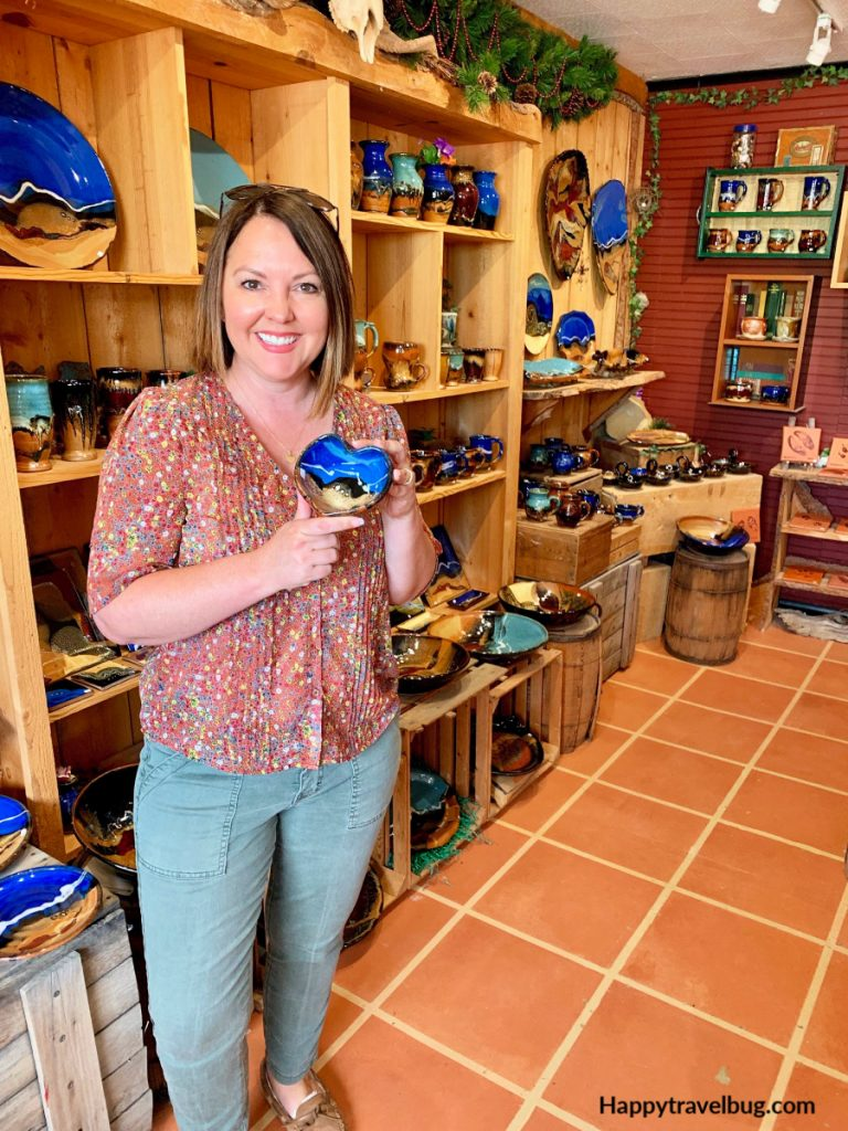 Woman in a pottery store holding a heart shaped bowl