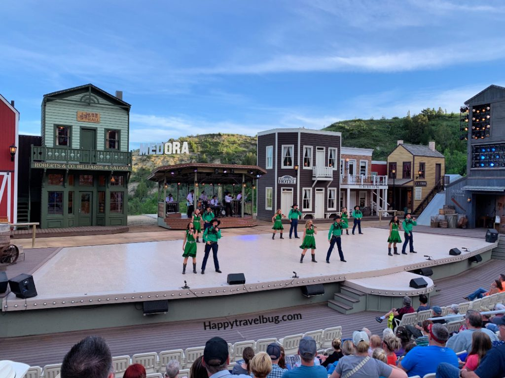 Dancers on a stage with a fake western town backdrop