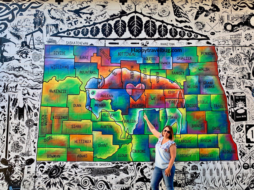 woman pointing to a mural of North Dakota